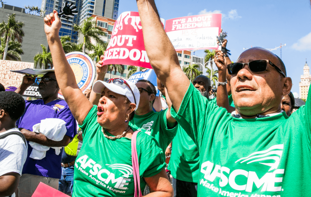 "AFSCME members at Florida rally holding signs reading ""It's about freedom."""